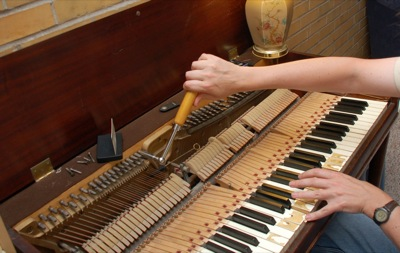 Person seated, tuning octaves with the tuning lever